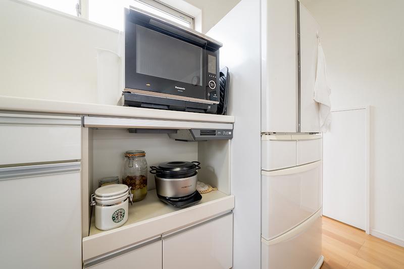白い冷蔵庫の左隣に電子レンジや炊飯器などを置いた棚がある
