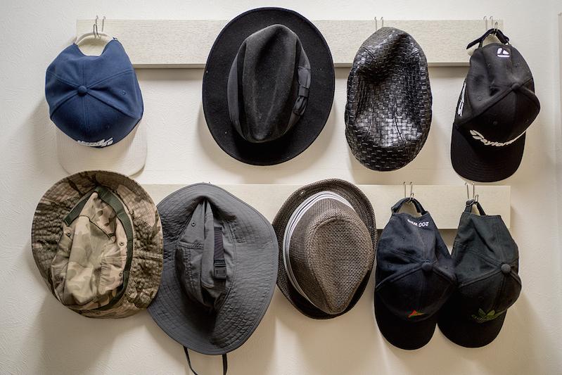 壁掛けのフックにかけられたハットなど帽子類