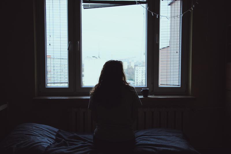 暗い部屋から外を眺める女性