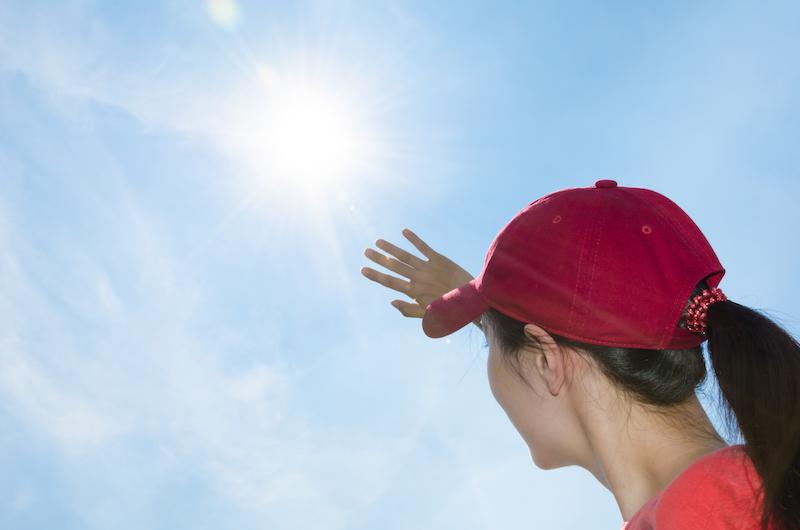 日差しに手をかざすキャップを被った女性