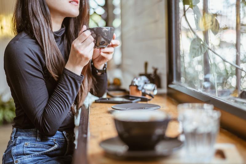 カフェで飲み物を飲む女性