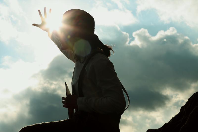 太陽に手をかざす女性