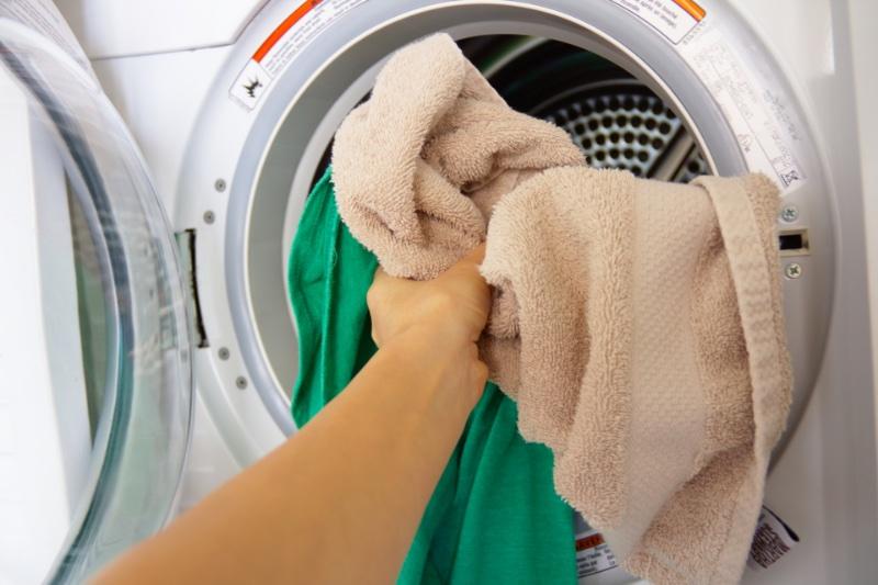 洗濯機にバスタオルなどを入れている