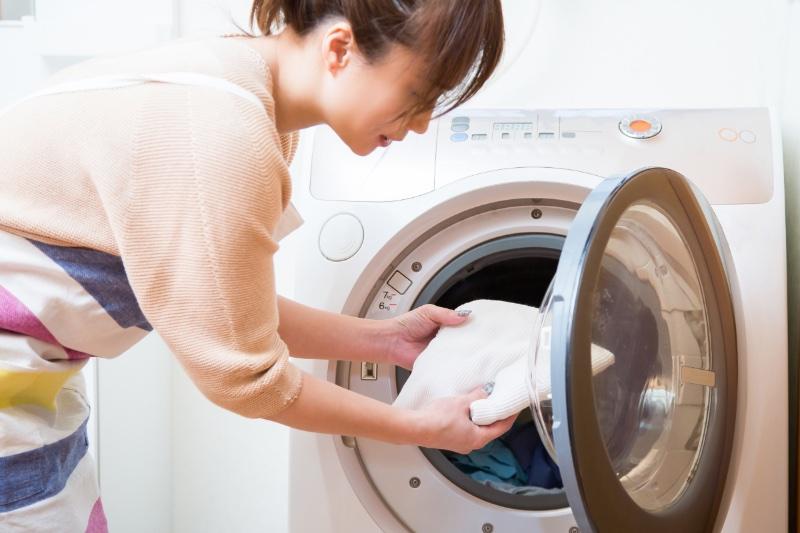 ドラム型洗濯機に洗い物を入れる女性