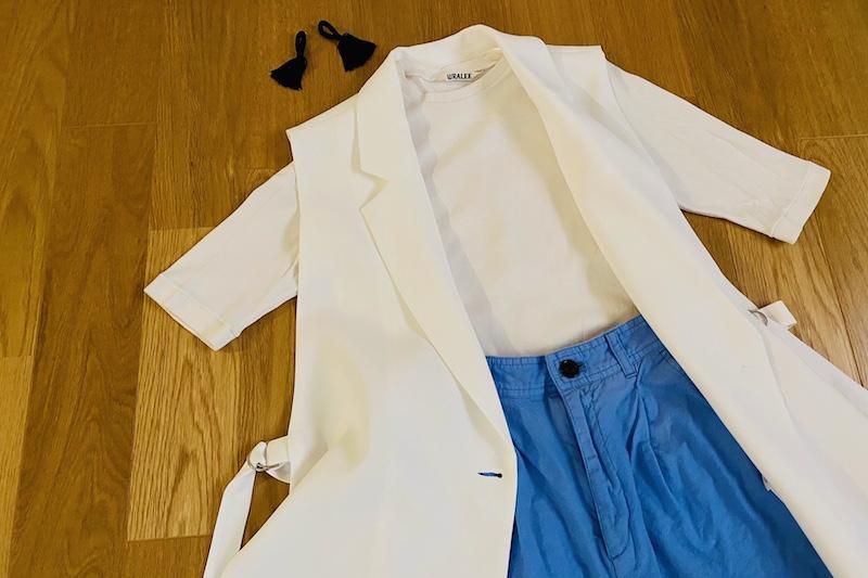 ZARAの白のスリットジレとと白いTシャツとブルーのカラーパンツと黒のタッセルピアスが床に置いてある