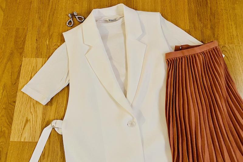 ZARAの白のスリットジレとブラウンの細いプリーツロングスカートとピアスが床に置いてある