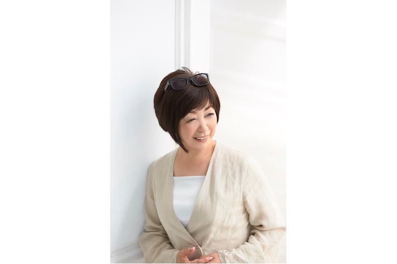 スタイリストの石田純子さんが、白のインナーに、ベージュの羽織ものを着て黒縁のメガネを頭にかけている