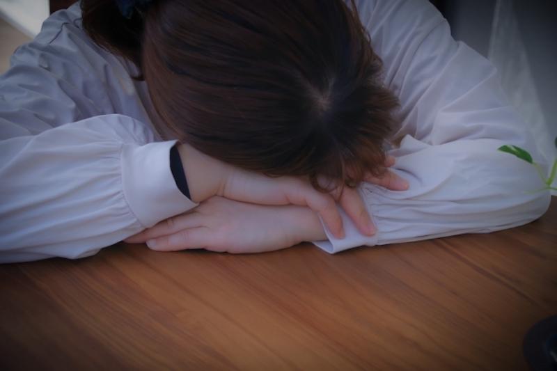 机に突っ伏して寝ている