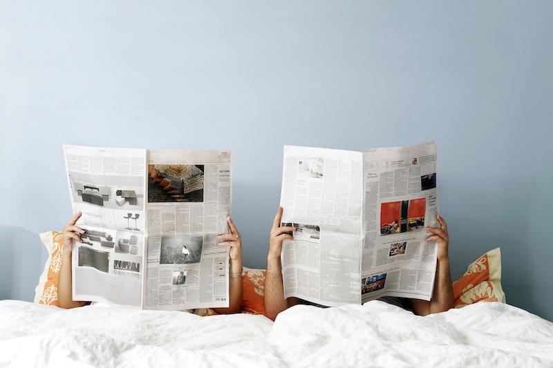 ベッドの中で新聞を読んでいる