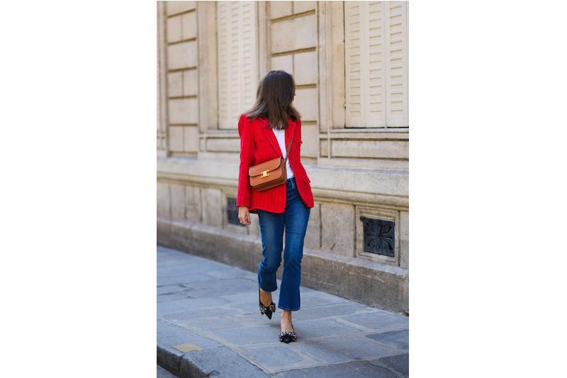 赤いジャケットに白のインナー、デニムパンツに黒のパンプスを着用した女性
