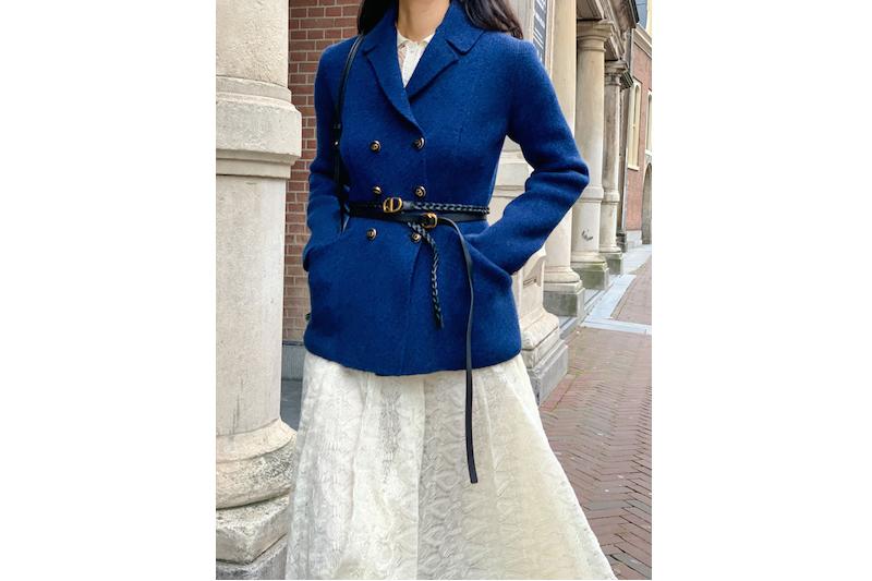 白のワンピースの上に羽織った青のジャケットの上から黒のベルトを巻いたファッションの女性
