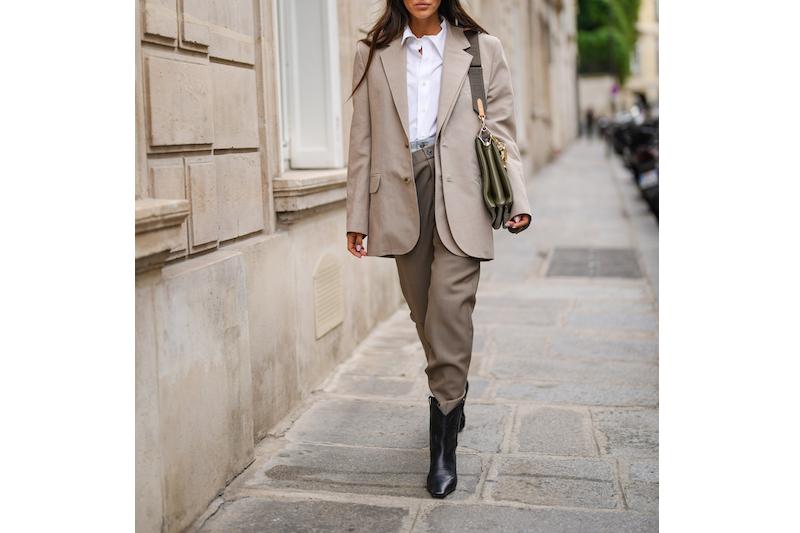 白シャツにベージュのジャケット、カーキのパンツ黒のブーツを着用した女性