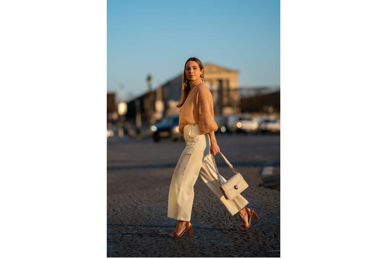 ベージュのニットに白のワイドパンツ、白のバッグ、ブラウンのサンダルを履いた女性