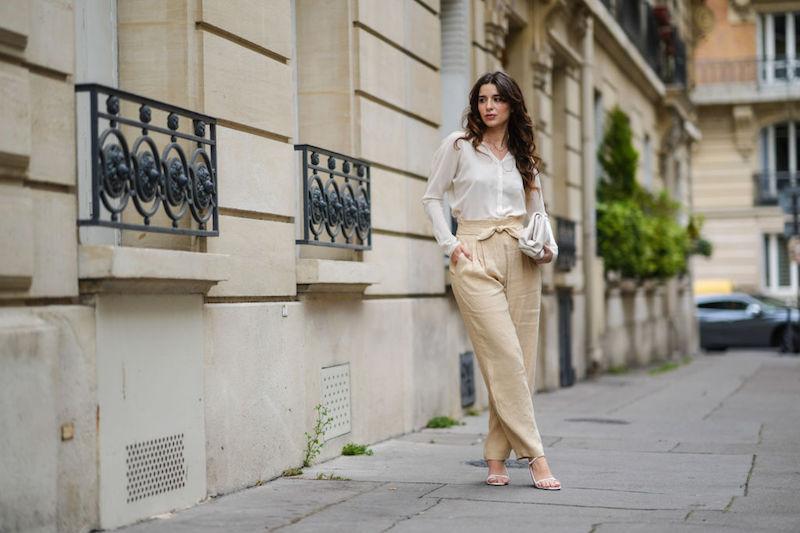白のブラウスにオフホワイトのリラックスパンツに白のバッグ、白のサンダルを着用した女性