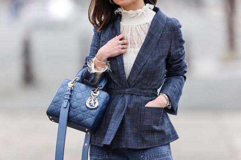 白のブラウスの上に紺色のジャケットを羽織ネイビーのバッグを持った女性