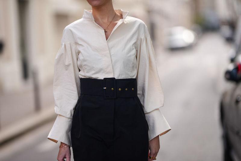 白のブラウスにベルトの付いた黒のスカートをはいた女性