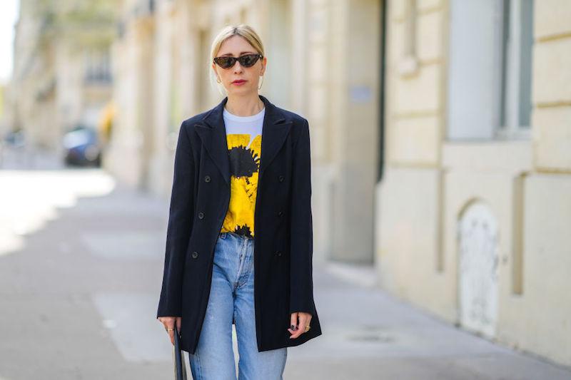 白のひまわり柄のTシャツにデニムパンツ、黒のジャケットを羽織サングラスをかけた女性