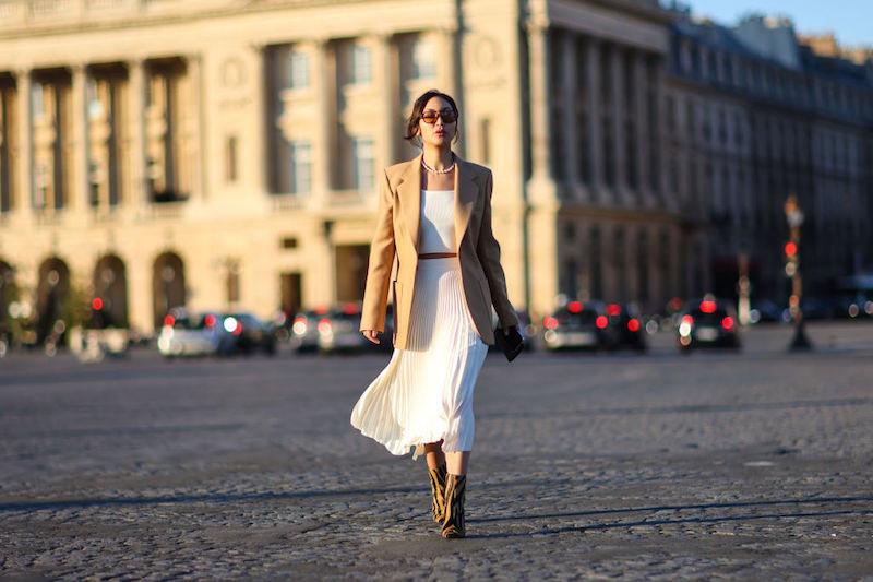 白のスカートとインナーにベージュのジャケット、兄松柄のショートブーツをはいた女性