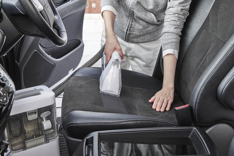 リンサークリーナーで車のシートを掃除している手元