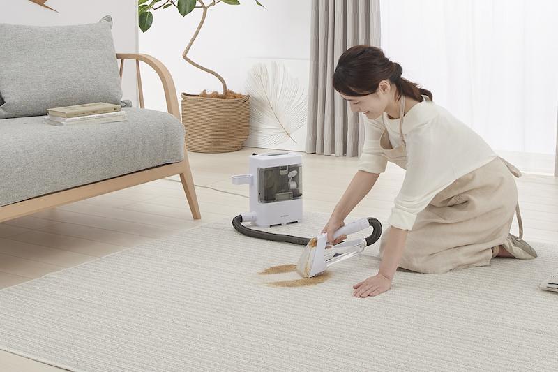 リビングで、リンサークリーナーを使ってカーペットの汚れを掃除している女性