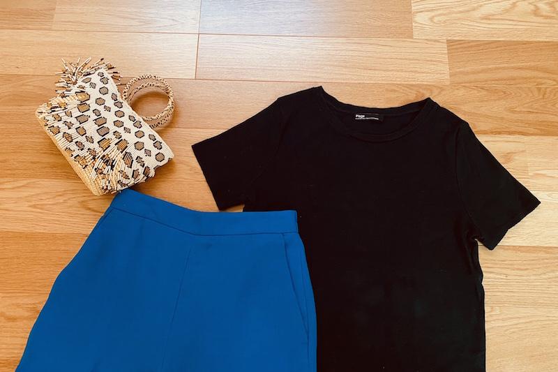 床に黒のTシャツとヒョウ柄のビーズのかごバッグとブルーのリネン素材のパンツが置かれている