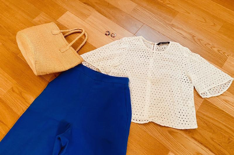 床にブルーのリネン素材のパンツと白のブラウスとかごバッグとピアスが置かれている