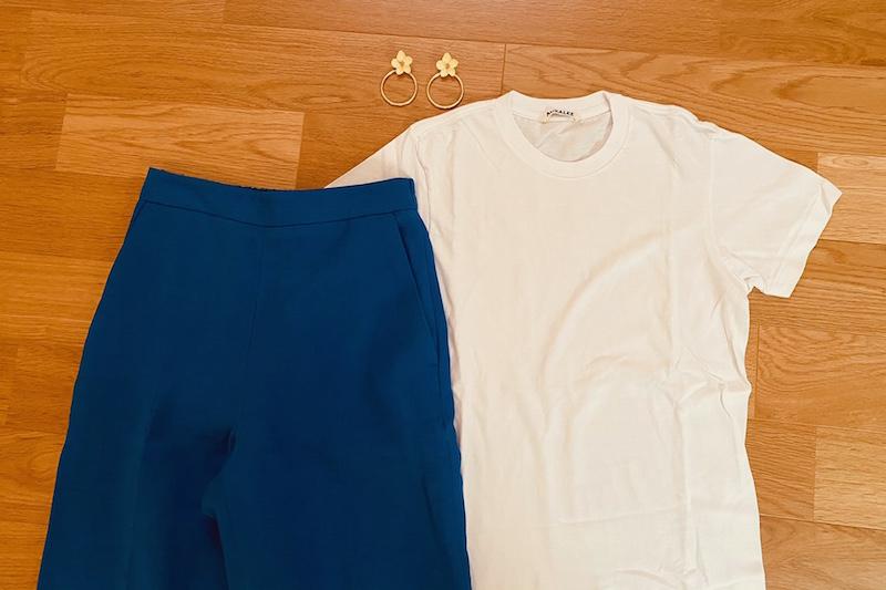 床に白のTシャツとブルーのリネン素材のパンツと黄色い花モチーフのピアスが置かれている