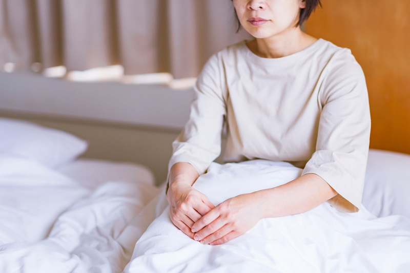 ベッドに座り、考え事をしているふうな女性