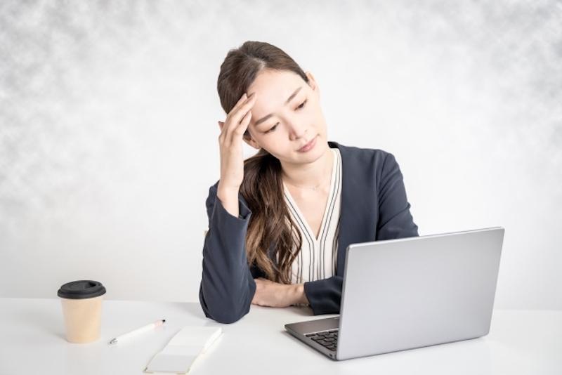 パソコンの前でおでこに手を当てる女性