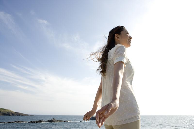 海と空をバックに立つ女性