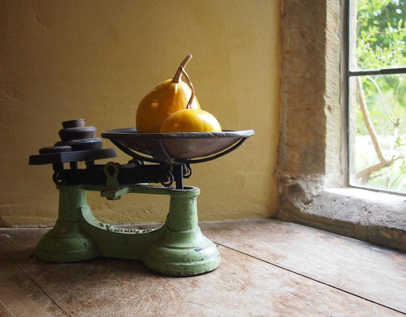 天秤に乗ったおもりと果物