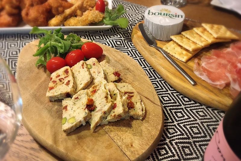 イケアのまな板ファシネーラに生ハムとクラッカー、バターなどが置かれ、奥には白い皿にチキンなどがのっている