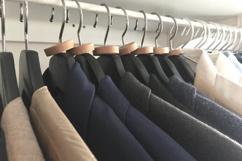 イケアのハンガーブメラングにスーツなどかけられて並べられたクローゼット