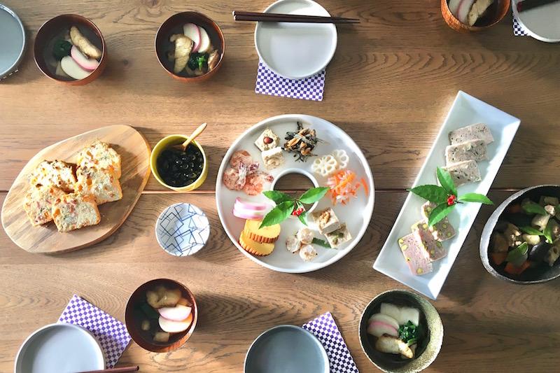 ドーナッツ型の白い皿に伊達巻や佃煮などおせち料理がもられ、お雑煮、黒豆の甘露煮、イケアのまな板ファシネーラの上にケークサレが置かれている