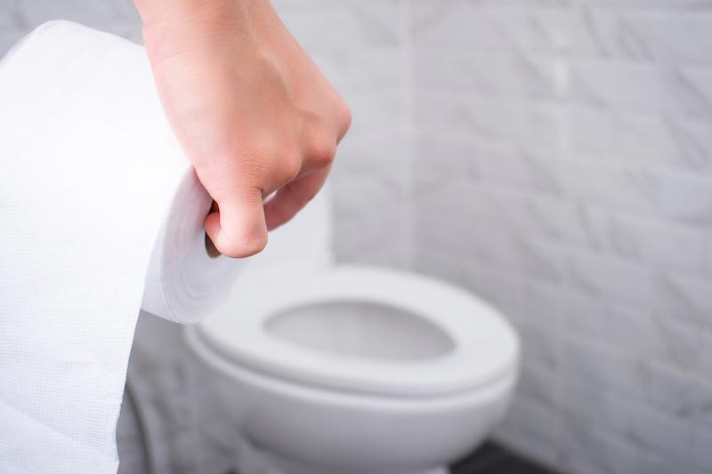 トイレでトイレットペーパーを持っている手