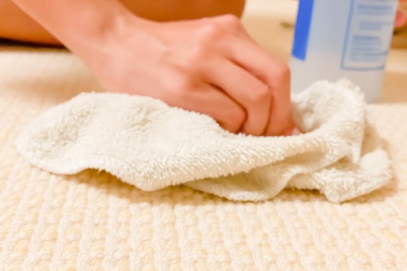 カーペットをタオルで拭いている