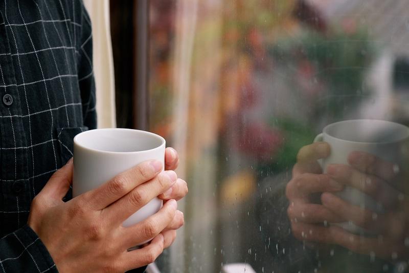 窓際でマグカップを手に雨降る外を眺める人の手元画像