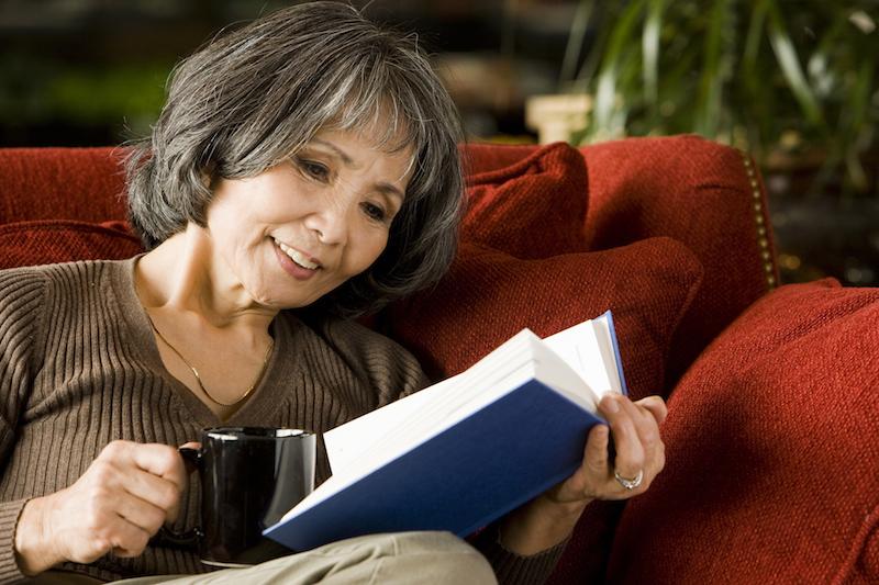 マグカップを片手に本を読みソファに座る女性