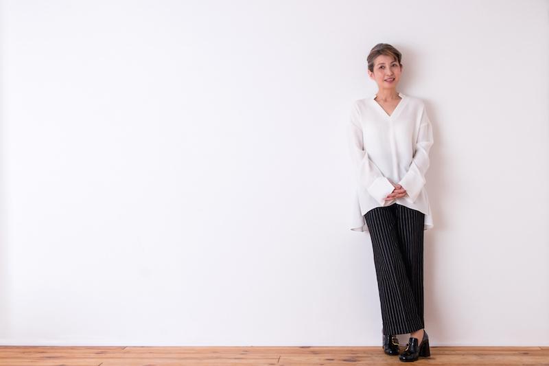 白いシャツにストライプの黒のパンツをはいた女性が壁にもたれかかっている