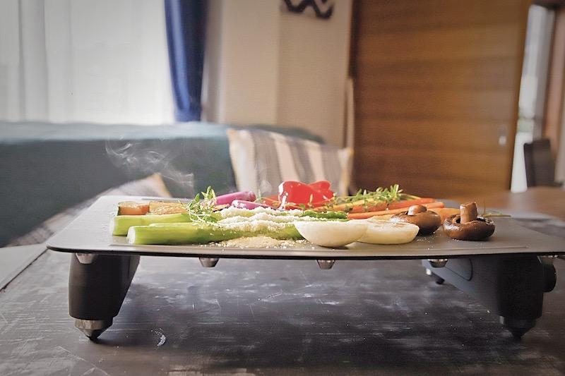 リビングのテーブルにあるアビエン『マジックグリル』の上で野菜などを焼いている