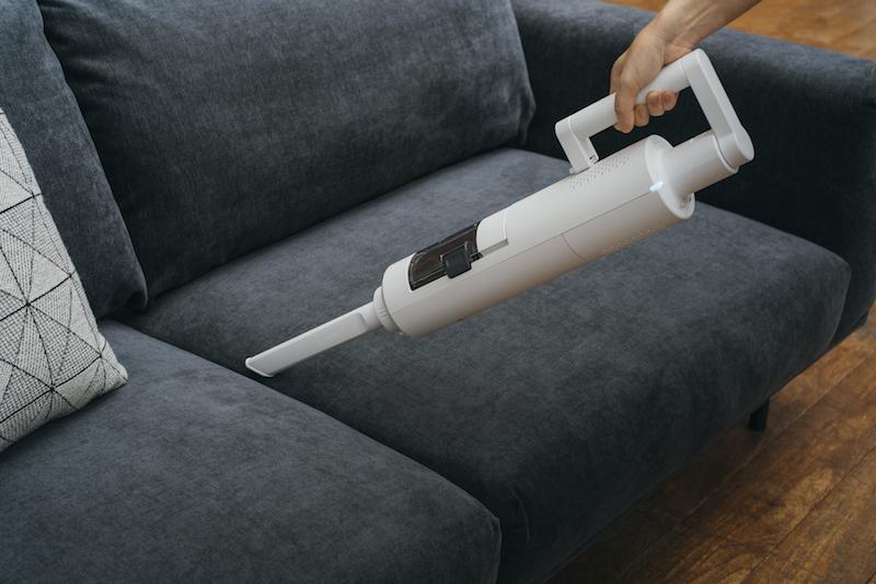 バルミューダ『BALMUDA The Cleaner』をハンディタイプとしてソファを掃除している手元