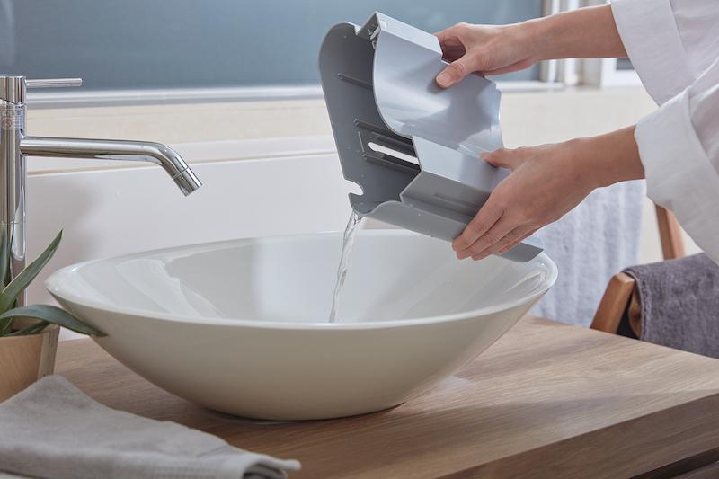 レコルト『部屋干し除湿機』に溜まったタンクの水を洗面台に出しているところ