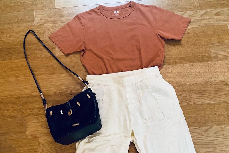 ユニクロの『クルーネックT(半袖)』27Orangeと白のパンツと黒い革バッグ