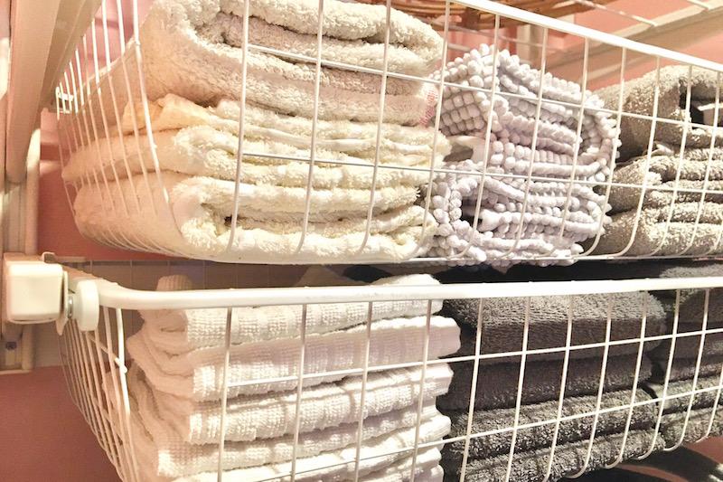 洗濯機の上の白い棚に白やグレーのタオルが入っている。