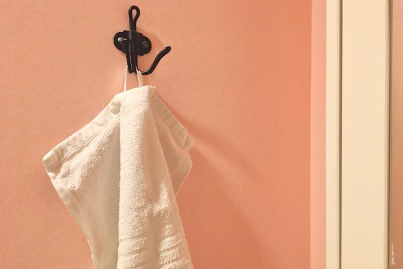 黒いフックに白いタオルが掛けてある