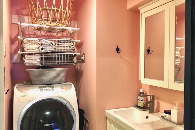 洗濯機の上の白い棚に白やグレーのタオルが入っていて、その上にはかごが置いてあり、横には白い洗面台がある