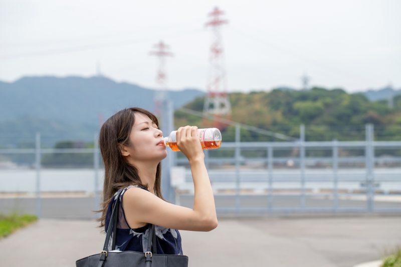 ペットボトルの麦茶を飲んでいる女性