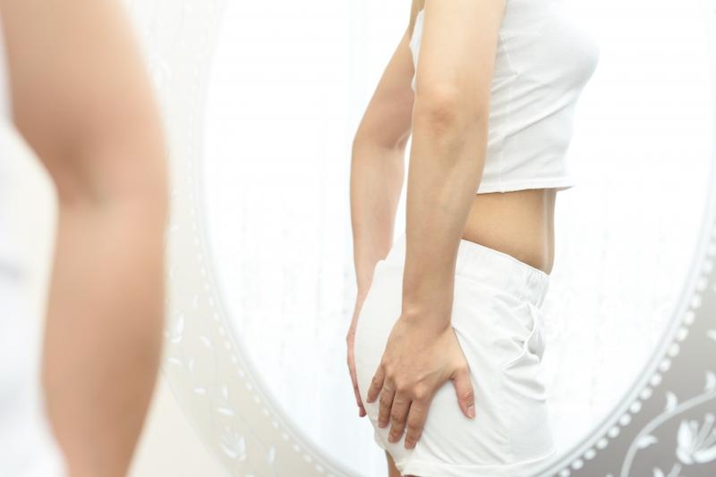 白い服を着た女性がお尻を押さえている
