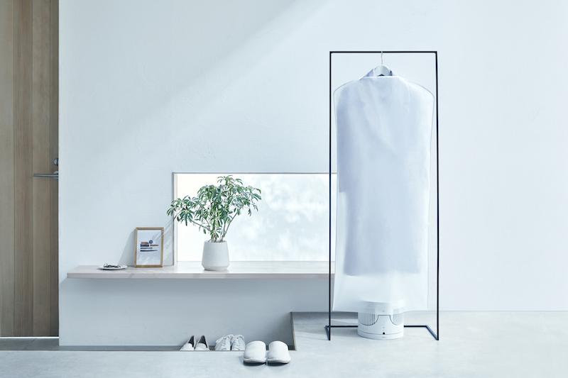 マクセルのオゾン除菌消臭器 オゾネオ部屋干しネクストを部屋の一角に掛けた洋服を除菌消臭している様子