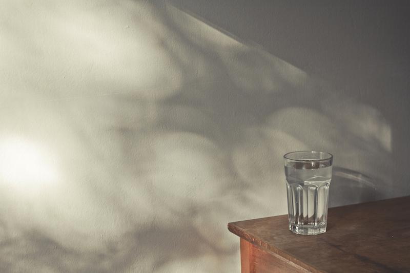 窓際の机に置かれたカップに入った水